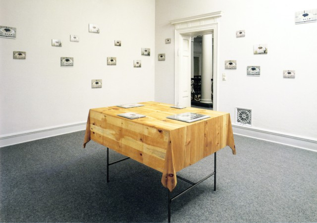 """Untitled (Tokyo Table)"", 1990, table with wooden table cloth, metal structure, picture frames with styrofoam packaging with photographs of a Japanese noodle dish, 97 x 120 x 81.5 cm table, 12.6 x 17.4 cm dish 1 18 x 24 cm dish 2, 20 x 30 cm dish 3, 28 x 35 cm dish 4 © Estate of Martin Kippenberger, Galerie Gisela Capitain, Cologne, Installation view at the Villa Merkel in Esslingen in 1996, photo: Uwe Seyl"